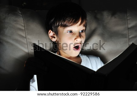 Kid reading book, light in darkness - stock photo