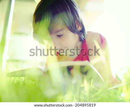 Kid reading book on summer grass meadow - stock photo
