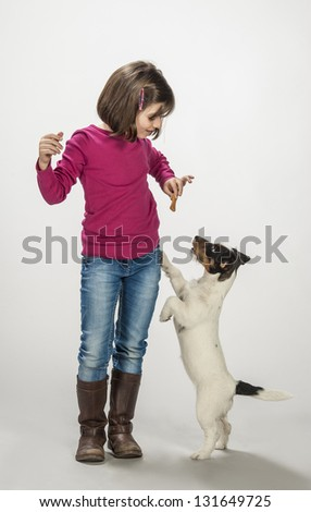 Kid rewarding her dog - stock photo