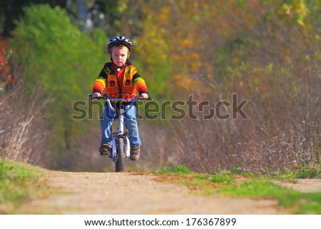 Kid rides his bike on dirt road in sunny autumn - stock photo