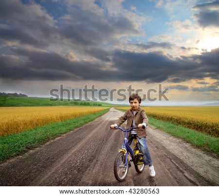 kid riding bicycle in the countryside - stock photo