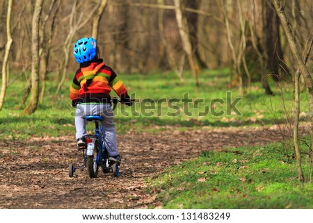 Kid riding his bike on the forest trail - stock photo