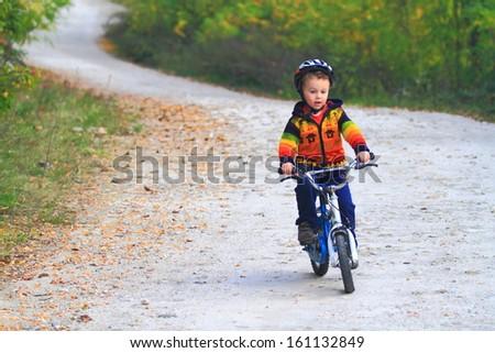 Kid riding his bike outdoor in autumn - stock photo