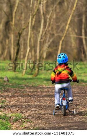 Kid riding his bike through forest in springtime - stock photo