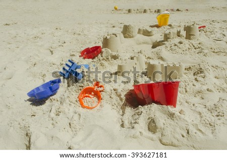 Kid's beach toys and sand castle - stock photo