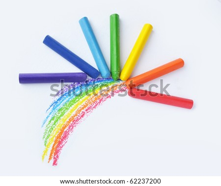 Kid's drawn rainbow and colorful crayons on white background - stock photo