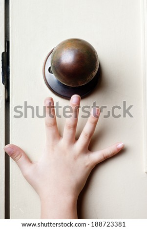 Kid's hand reaching up for the door knob to open it  - stock photo