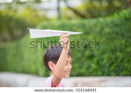 Kid's hand taking  playing plane paper in the park - stock photo
