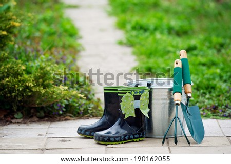 Kid's rain boots and garden utensils in the spring garden - stock photo