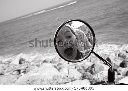 Kid's reflection in the motorbike's mirror