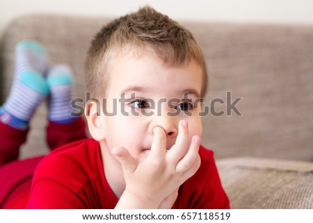Kid scratching a finger in his nose. Itching boy lying on his stomach with head in hands and legs bent at the knees while watching TV