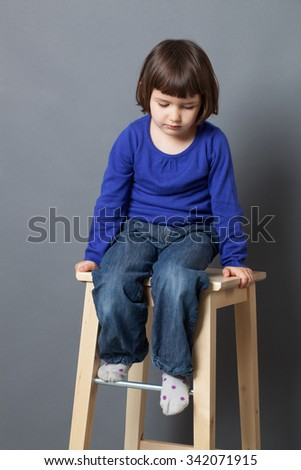 kid serenity concept - thoughtful preschool child looking down in sitting on high wooden stool for serene wellbeing,studio shot - stock photo