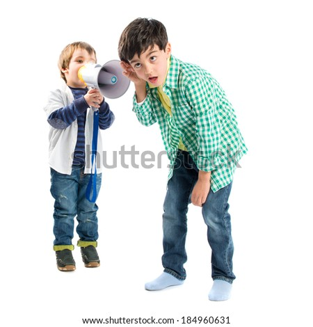 Kid shouting at his friend by megaphone over white background - stock photo