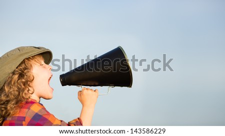 Kid shouting through vintage megaphone. Communication concept. Blue sky background as copy space for your text - stock photo