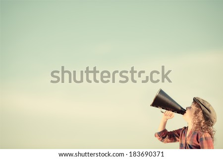 Kid shouting through vintage megaphone. Communication concept. Retro style - stock photo