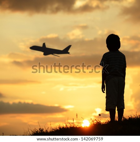 Kid silhouette on meadow looking at airplane in air - stock photo