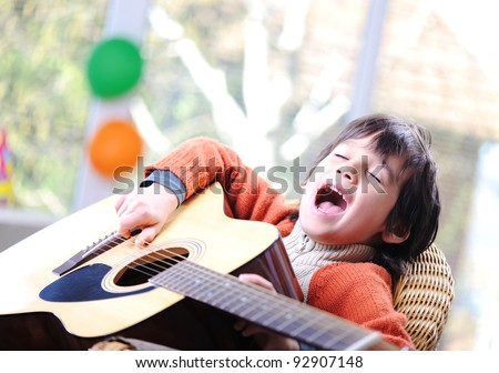 Kid singing and playing guitar at home - stock photo