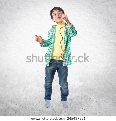 Kid singing over textured background  - stock photo