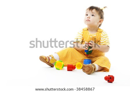 Kid sit and play with toy, dressed in yellow pajama, isolated on white - stock photo