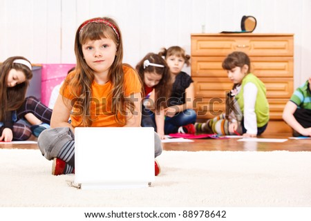 Kid sitting in front of laptop - stock photo