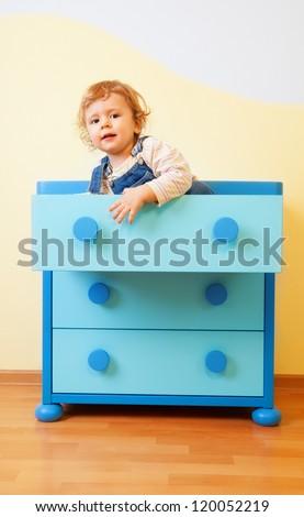 Kid sitting inside blue opened cabinet box - stock photo