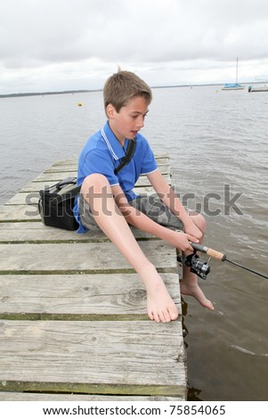 Kid sitting on a pontoon with fishing rod - stock photo