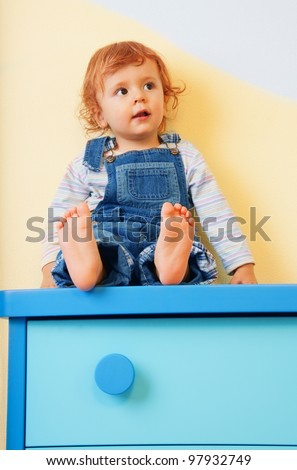 kid sitting on furniture - on the chest of drawers - stock photo