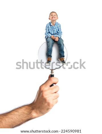Kid sitting on magnifying glass - stock photo
