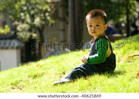 kid sitting on the grass