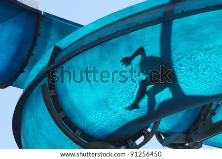 Kid sliding a blue Waterslide - stock photo