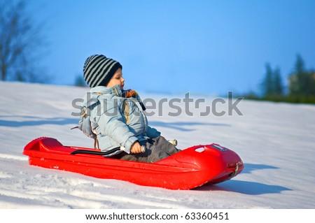 Kid sliding in the snow. - stock photo