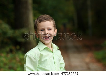 Kid smiles sincerely while posing in the park