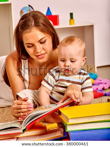 Kid son with mother baby boy lying on floor and read book.