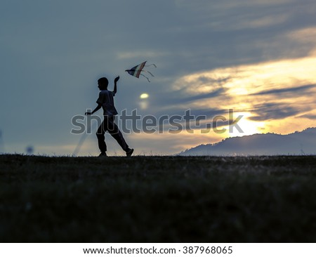 kid spending time on summer meadow by sunset