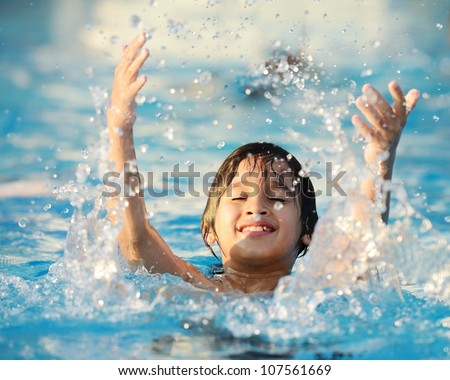 Kid splashing on summer pool - stock photo