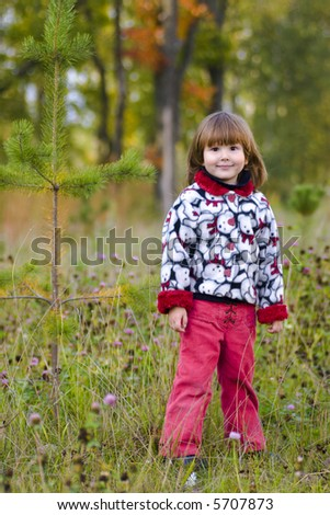 Kid standing in the fall forest wearing casual closes and looking at you