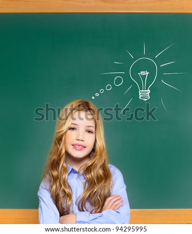 kid student girl on green school blackboard and drawn light bulb idea [Photo Illustration] - stock photo