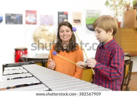 Kid studying percussion instrument vibraphone, teacher next to him - stock photo