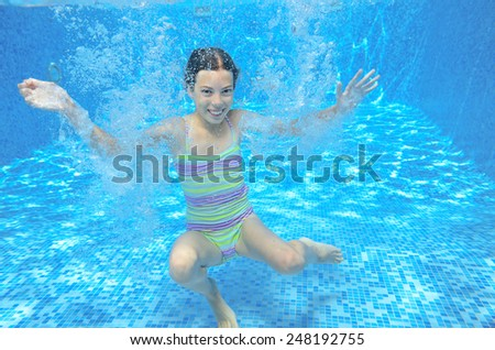 Kid swims in pool underwater, girl swimming, playing and having fun, children water sport  - stock photo