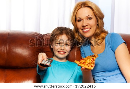 Kid switching TV and mother with pizza - stock photo