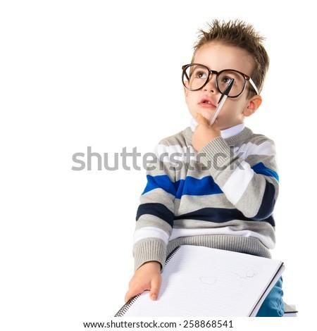Kid thinking on books - stock photo