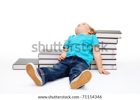 Kid tiered of education lay exhausted on the floor and steps made of books - stock photo