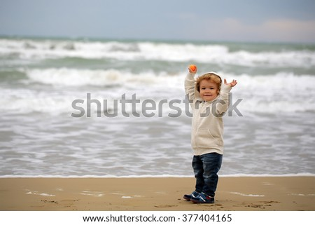 Kid tiny little child baby boy joyful fair-haired in jeans and white hooded coat holding arms upward with orange ball on windy murky day on blurred seascape background, horizontal picture