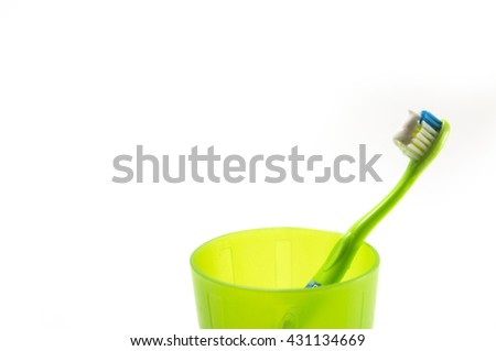 Kid toothbrushes in plastic glass isolated on white - stock photo