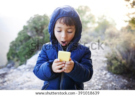 kid using a mobile phone in the nature - stock photo