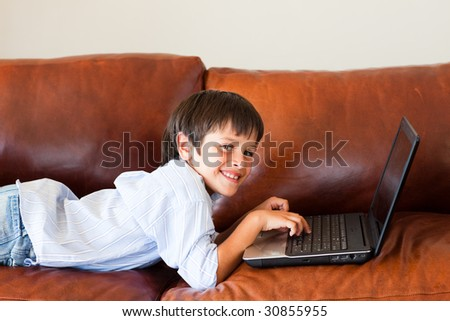 Kid using his laptop at home - stock photo