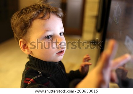 Kid using interactive touch screen in a museum - stock photo