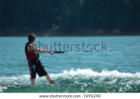 Kid wakeboarding on a lake - stock photo