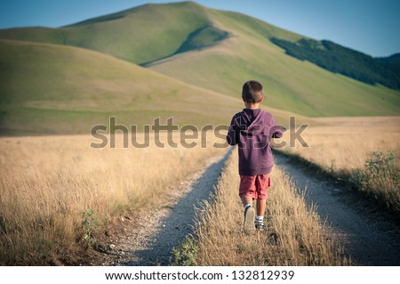 Kid walking alone outdoors. Castelluccio di Norcia, Monti Sibillini Park, Italy. - stock photo