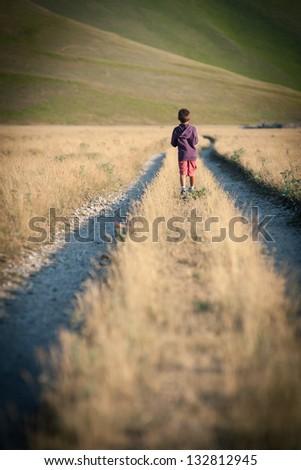 Kid walking alone outdoors. Castelluccio di Norcia, Monti Sibillini Park, Italy. - stock photo